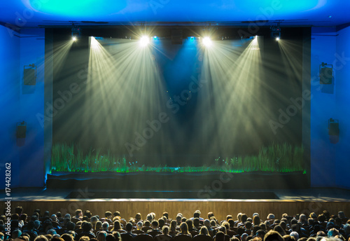The stage before the show. The audience in the hall. The spotlight on stage. Theatre.