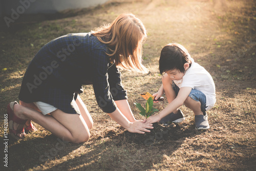 Fotografie, Obraz  Cute Asian child and mother planting young tree on the black soil