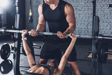 Trainer Helping Woman Weightli...