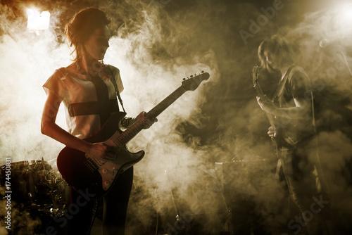 Plakat Dziewczyna-gitarzysta gra solo.