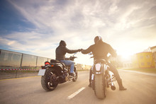 Two Bikers Ot Motocycles Handshaking With Knuckle On Road At Sunshine