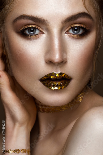Plakat piękna dziewczyna ze złotym błyszczącym makijażem i gwiazdami na ustach. Piękna twarz. Zdjęcie zrobione w studio.