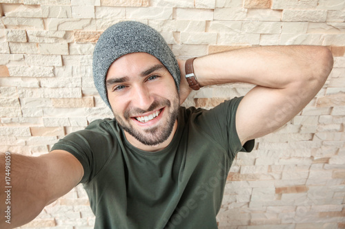 Fotografía  Young man taking selfie against brick wall background
