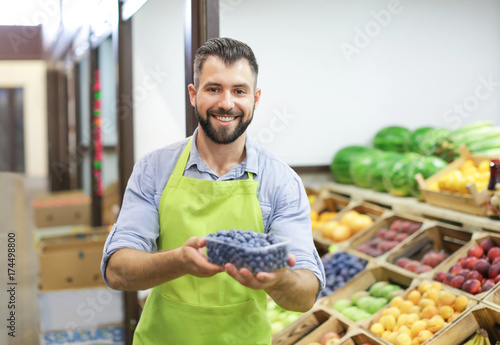 Seller in apron holding plastic container with blueberries at market