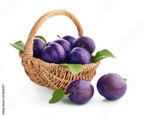 Wicker basket with ripe plums on white background