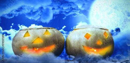 Composite image of illuminated jack o lanterns on table Plakat