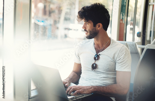 Bearded hipster guy is working on a portable computer connected to public wi-fi while sitting in a city bus. Young attractive male is looking at the window while typing messages by a laptop.