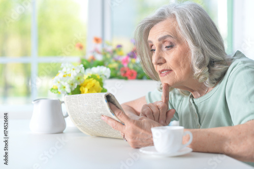Foto op Canvas Kruidenierswinkel Beautiful old woman reading a newspaper