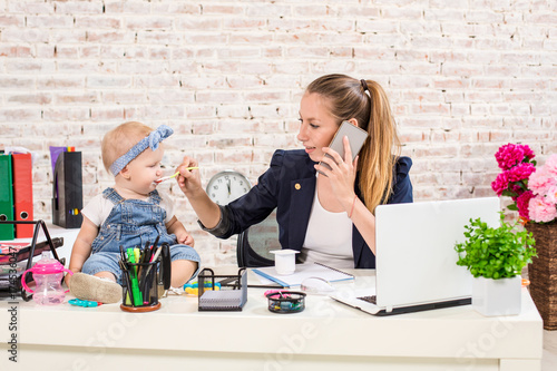 Fotografía  Family Business - telecommute Businesswoman and mother with kid is making a phon