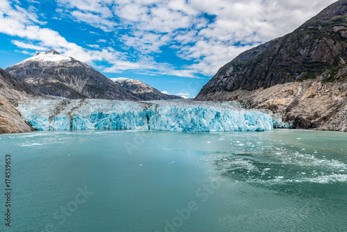 Fotografiet Long distance view of an Alaskan glacier with aqua icy waters