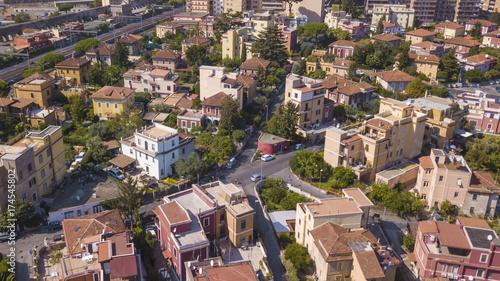 Zdjęcie XXL Widok z lotu ptaka na pałace wykorzystywane do celów mieszkalnych na wschodzie miasta Rzym. Pomiędzy domami i ulicą rośnie wiele wysokich drzew, które nadają metropolii trochę zielonego i czystego powietrza.