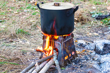 Smoked Pot On A Camp Stove. The Pan Is Covered With A Lid