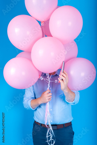 Young handsome man in blue shirt holding pink air balloons