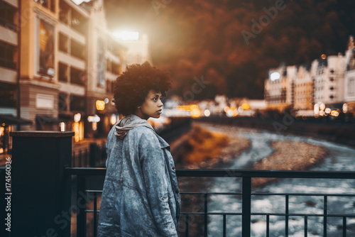 Valokuva  Beautiful curly afro-American lady with curly hair in jeans jacket with hood loo