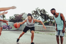 Young Boy Playing Basketball Game With Friends