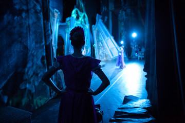 ballet, dancing, magic concept. in ghostly blue light tender silhouette of slender ballerina wearing pink dress with short sleeves waiting for her turn backstage