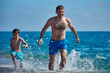 Caucasian dad and son are running in the water along the sea shore.