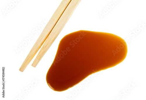 Splashes of soy sauce and chopsticks isolated on white background