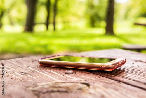 Fototapeta  Macro closeup of lost generic light pink rose gold smartphone, phone left, forgo