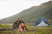 Couple Sitting Near Campfire A...