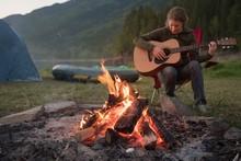 Woman Playing Guitar Near Camp...