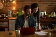 Couple reading document while using laptop