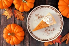 Slice Of Pumpkin Cheesecake With Whipped Cream, Overhead Table Scene On A Rustic Wood Background