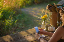 Woman Sitting At Picnic Bench In Autumn With Smartphone And Fresh Cut Wildflowers