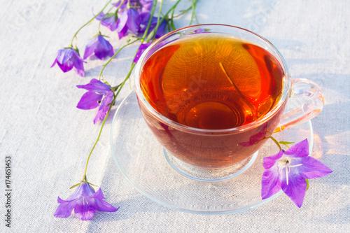 filizanka-herbaty-i-niebieskie-kwiaty-dzwonku-na-serwetce-lnianej