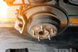 modern car disc brake to be fixed at garage or automotive service station with sunlight effect