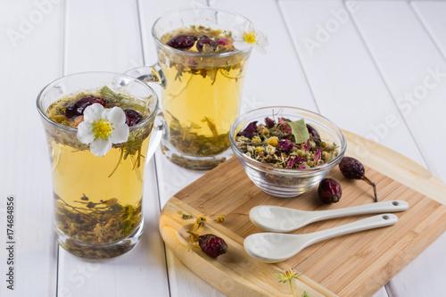 herbata-z-ziol-i-kwiatow-w-dwoch-szklanych-kubkach-obok-ziola-i-biale-lyzeczki-na-desce