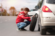 Young upset man changing tyre wheel on cityroad