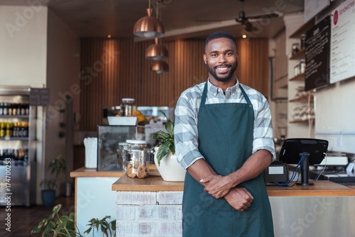 Fotografía  Smiling African entrepreneur standing at the counter of his cafe