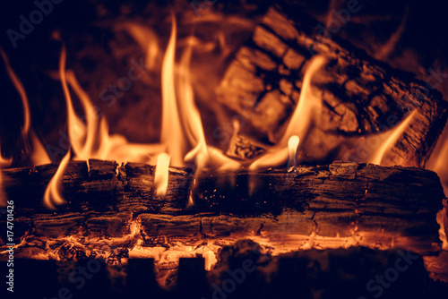 Fotografiet  Wood in the flames of cozy fireplace