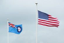 The American Flag Blows Side By Side With The Royal Air Force Flag In The Wind