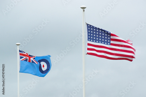 Obraz na plátně The American flag blows side by side with the Royal Air Force flag in the wind