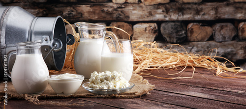 Poster Dairy products milk products. tasty healthy dairy products on a table on. sour cream in a bowl, cottage cheese bowl, cream in a a bank and milk jar, glass bottle and in a glass