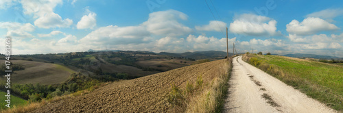 Panoramic view of a rural landscape with plowed fields and white country road