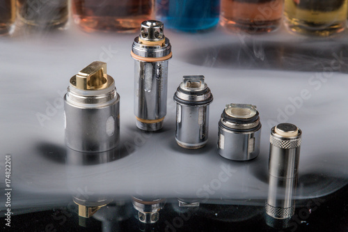 Photo Electronic cigarette steel coils in a row with e-juice bottles in the background