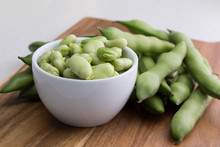 Close Up Fresh Raw Broad Beans In A White Bowl On A Wooden Cutting Board Surface
