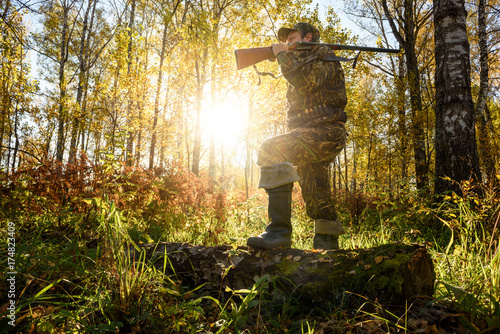 Autocollant pour porte Chasse A hunter with a gun in the forest at dawn.