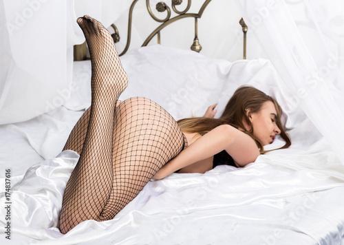 Zdjęcie XXL Seksowna piękna kobieta w zmysłowej bielizny i siatki pantyhose cieszy się w łóżku