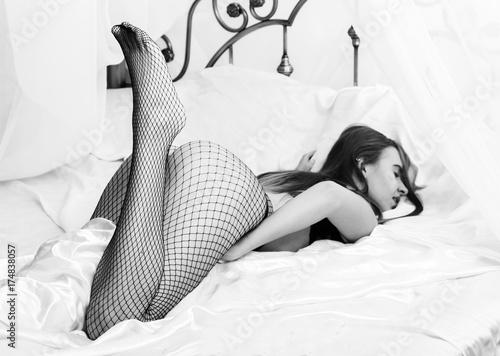 Zdjęcie XXL Seksowna piękna kobieta w zmysłowej bielizny i siatki pantyhose cieszy się w łóżku. czarny i biały