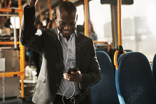 African businessman reading texts and wearing earphones on a bus