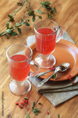 Two cups of hot berberis tea, on wooden background. Wallpaper Mural
