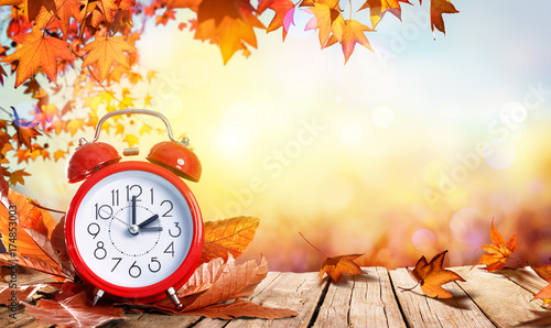 Daylight Savings Time Concept - Clock And Leaves On Wooden Table