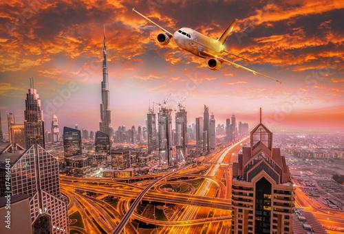 Fototapeta Samolot lata nad Dubaj przeciw kolorowemu zmierzchowi w Zjednoczone Emiraty Arabskie