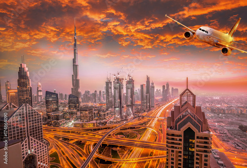 Poster Moyen-Orient Airplane is flying over Dubai against colorful sunset in United Arab Emirates