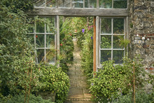 The Entrance To An Old Victorian Greenhouse With Cobbled Path
