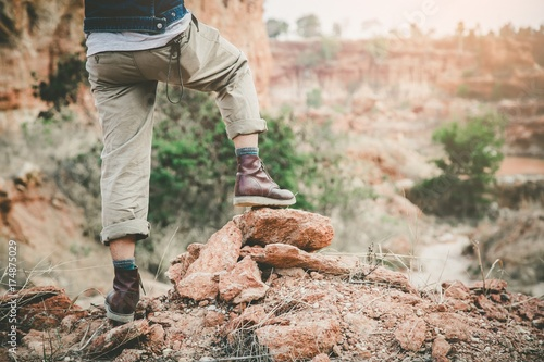 young hiker legs on mountain peak cliff